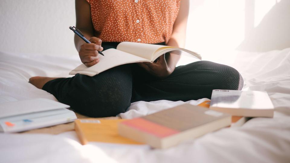 Concurso Prefeitura de Nova Brasilândia D'Oeste: a imagem mostra mulher sentada na cama com livros e cadernos