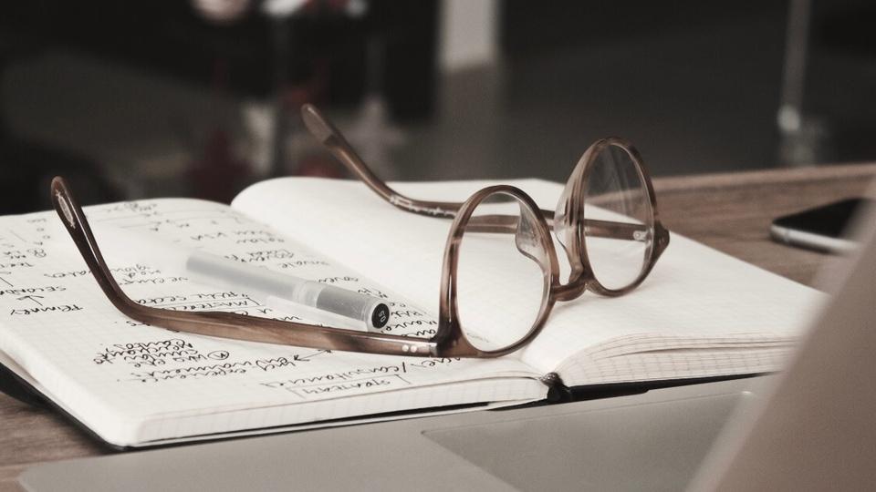Concurso Prefeitura de Nova Campina: óculos e caneta em cima de caderneta aberta