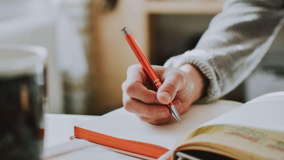 Concurso Prefeitura de Nova Olímpia – MT: pessoa segurando uma caneta ou grafite e anotando alguma coisa num caderno