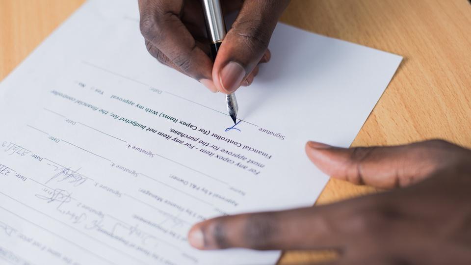 Concurso Prefeitura de Ouro Fino - pessoa segurando papel e escrevendo com a mão direita; foco nas mãos e folha de papel.