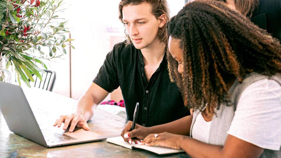 Concurso Prefeitura de Padre Paraíso - MG: grupo de jovens em frente ao notebook; moça escrevendo em caderno e rapaz usando o notebook