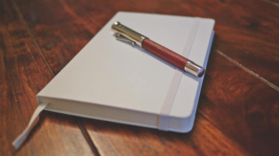Concurso Prefeitura de Pedrinópolis - MG: caderninho com caneta sobre mesa de madeira.