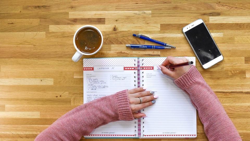 Concurso Prefeitura de Pedro Régis: pessoa escrevendo em um caderno. Na mesa, há também canetas, um celular e uma xícara de café
