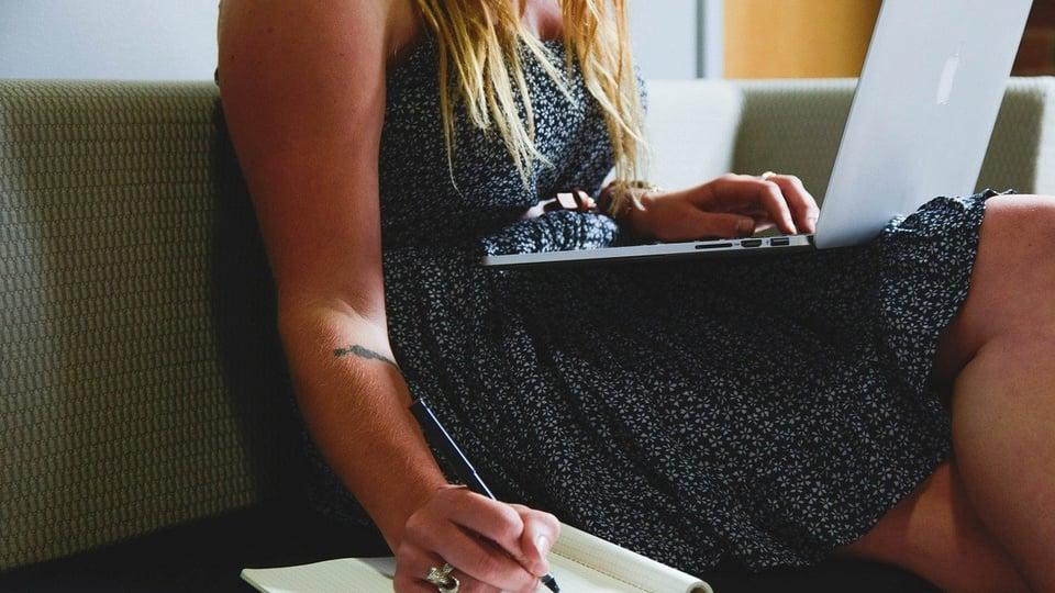 Concurso Prefeitura de Pimenta - MG: mulher sentada em sofá, com notebook no colo, escrevendo em pedaço de papel