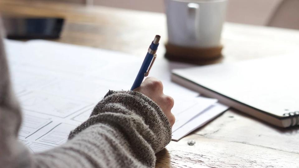 Concurso Prefeitura de Pontes Gestal: a imagem mostra pessoa escrevendo em caderno apoiado na mesa em frente à caneca