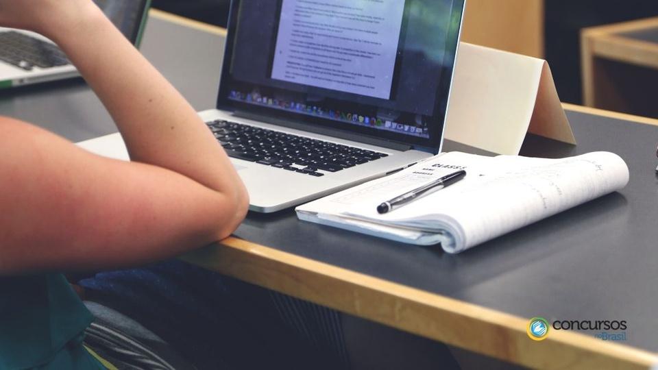Processo seletivo Prefeitura de Porto Belo: um notebook ligado numa mesa, caderno aberto e caneta e parte de uma pessoa em que só se vê o braço direito com o cotovelo repousando sobre a mesa