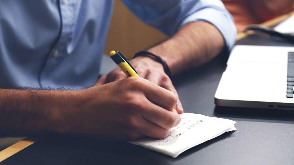Concurso Prefeitura de Quilombo - SC: homem, com roupa social, escrevendo em um caderno que está sobre a mesa. Ele está sentado. Sua caneta é amarela com detalhes em preto. No lado direito, é possível ver um notebook.