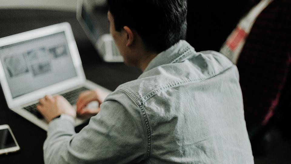 Concurso Prefeitura de Rinópolis - SP: #PraCegoVer Com camisa jeans, homem digita em notebook. Ele está de costas.