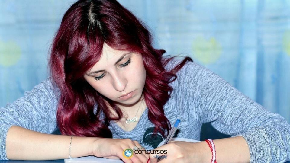 concurso prefeitura de santa maria: mulher escrevendo em folha de papel; foto com a logomarca do Concursos no Brasil