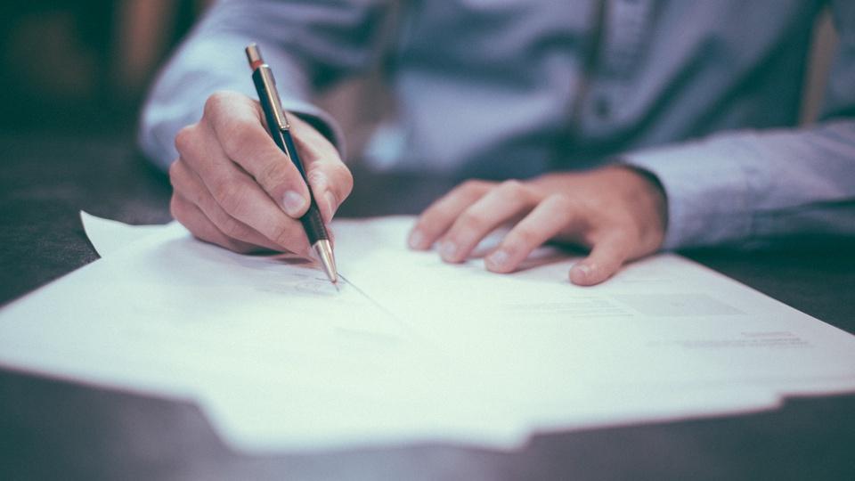 Concurso Prefeitura de São Pedro do Turvo - SP: papéis em cima de mesa; homem escreve em um deles
