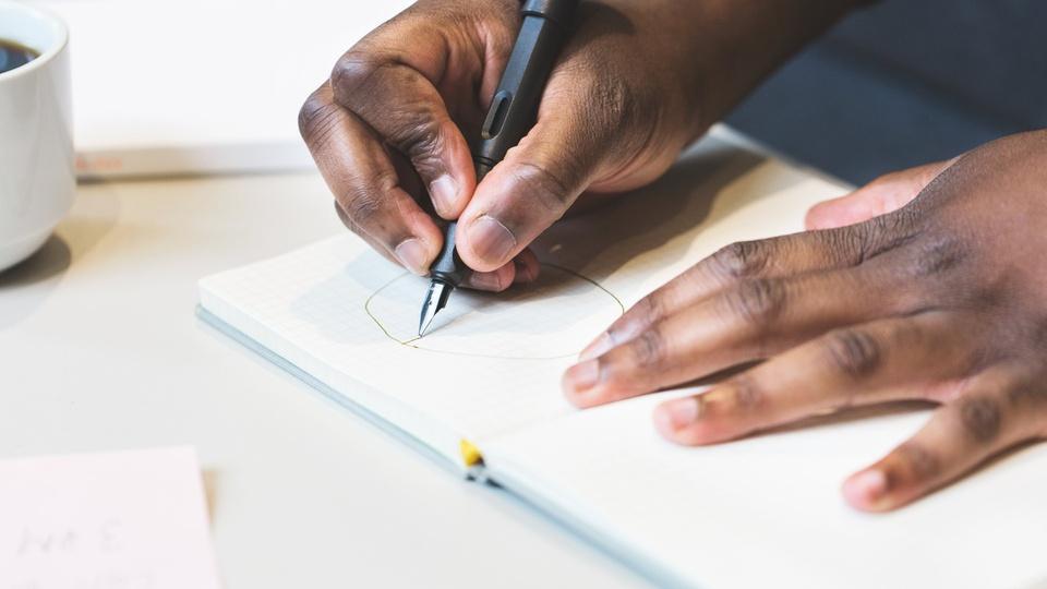 Concurso Prefeitura de Torrinha - SP: mão masculina escrevendo em folha de papel