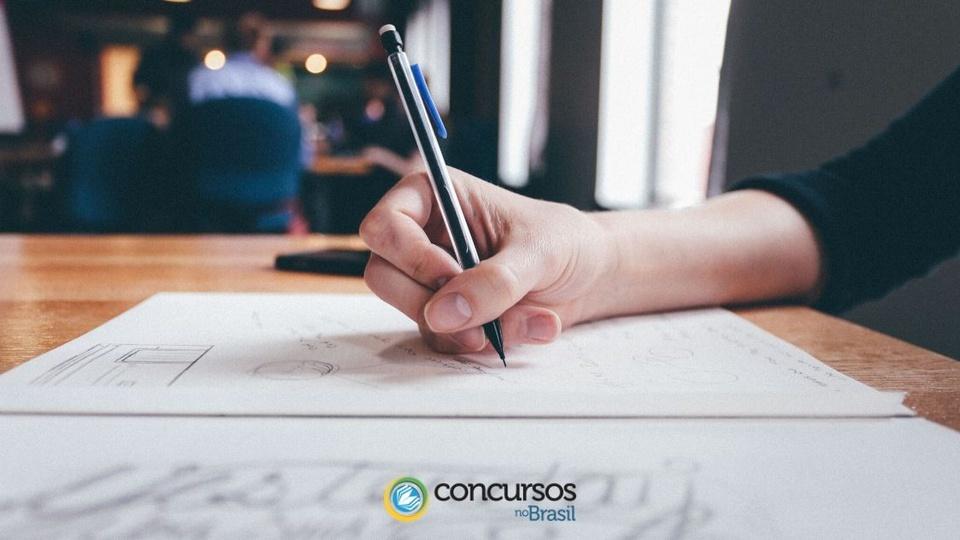 concurso prefeitura de vacaria: foco em mão escrevendo em folha de papel