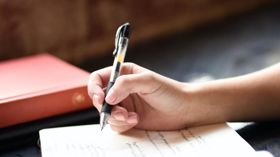 Concurso Prefeitura de Valentim Gentil - SP: enquadramento fechado em mão escrevendo em caderno