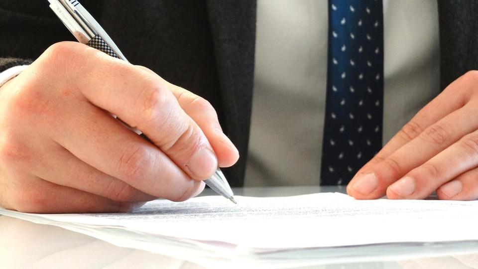 Concurso Prefeitura de Vitória: imagem de um homem de terno, segurando uma caneta e preenchendo um papel