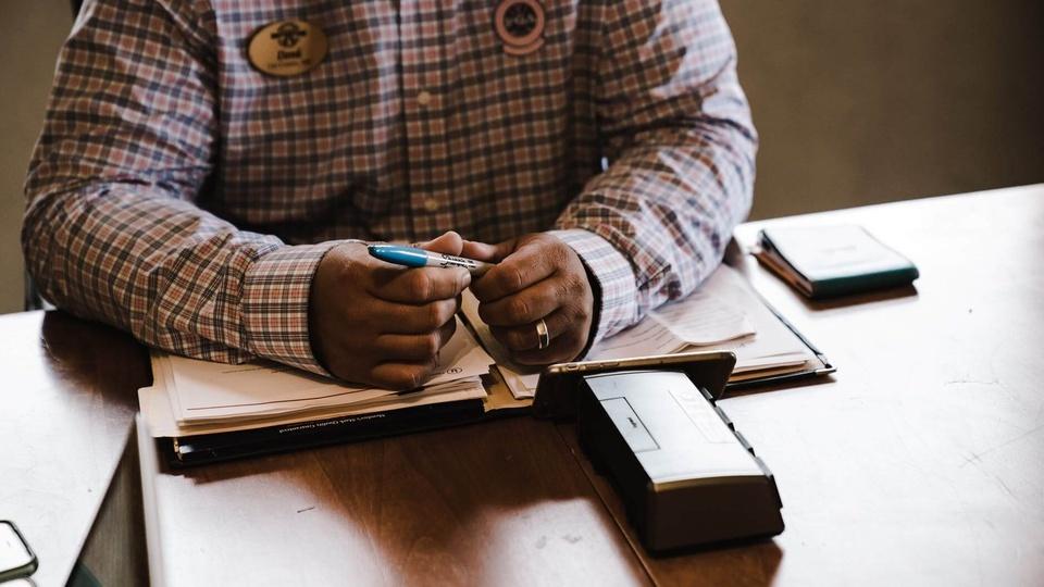 concurso Prefeitura de Votuporanga: homem sentado, com os braços sobre livros, e caneta em mãos