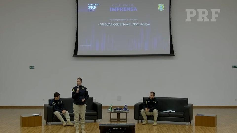concurso prf: a imagem mostra espaço com sofá, dois homens sentados, uma mulher em pé segurando microfone e um telão atrás dela