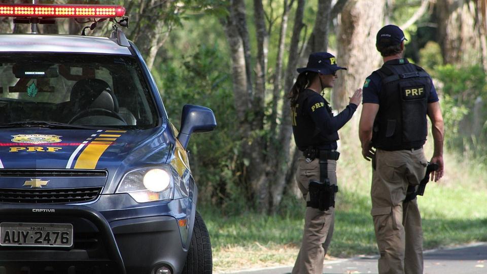 concurso prf: a imagem mostra dois policiais rodoviários conversando ao lado de viatura