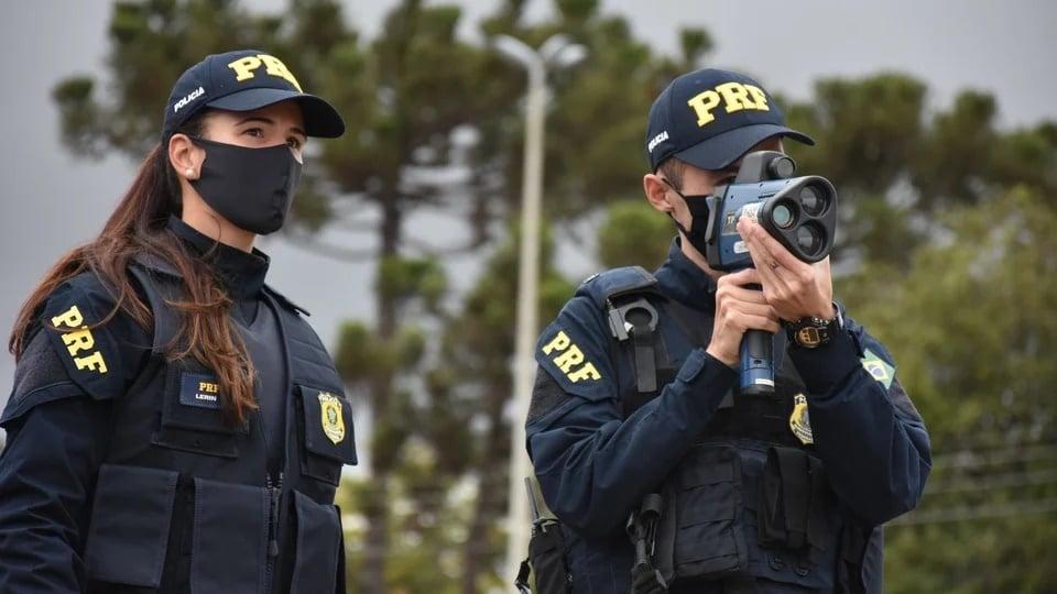 Língua estrangeira no concurso PRF: enquadramento em dois policiais rodoviários federais. Um deles está usando equipamento para medir velocidade de veículos