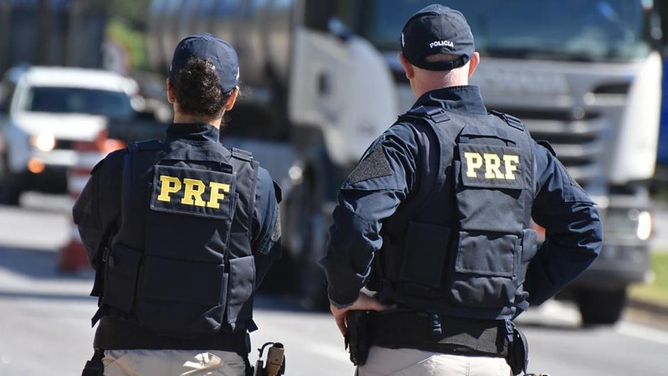 concurso prf: a imagem mostra dois policiais rodoviários fardados e de costas com boné na cabeça