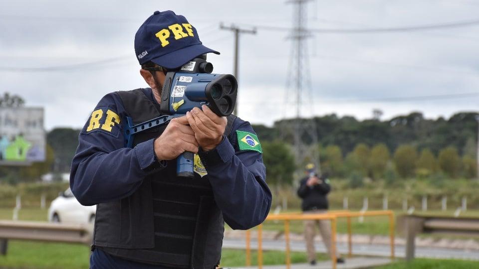 Comissão já concluiu o projeto básico do concurso PRF: Policial Rodoviário Federal usando aparelho para medir velocidade de carros