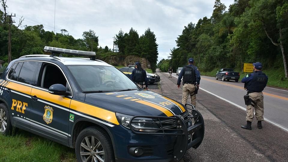concurso PRF: a imagem mostra viatura da PRF em primeiro plano e ao fundo três policiais rodoviarios federais parados numa estrada