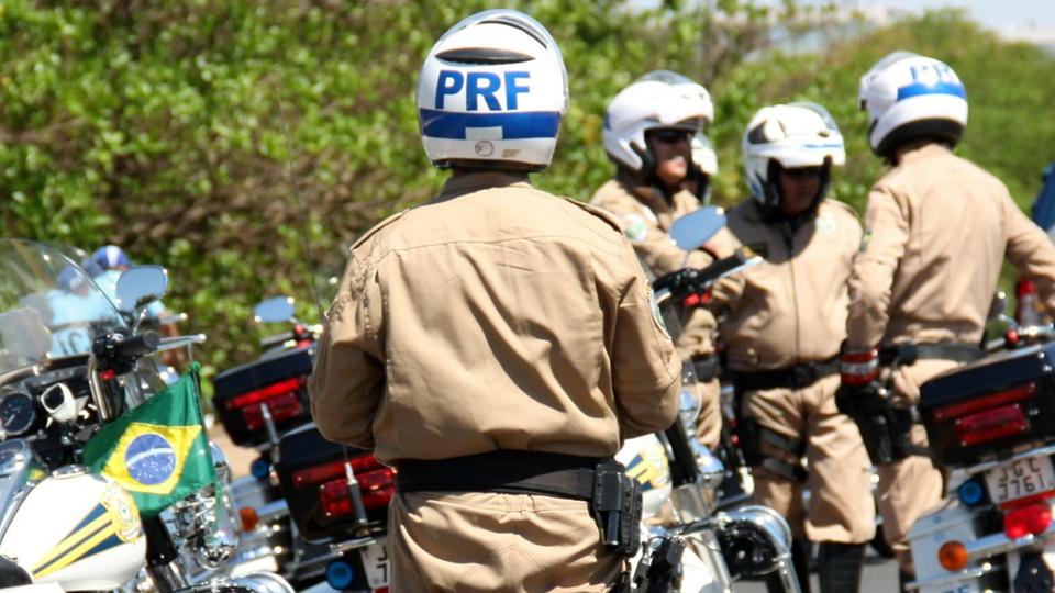 Candidatos convocados no concurso PRF e PF: policial rodoviário federal virado de costas para a câmera