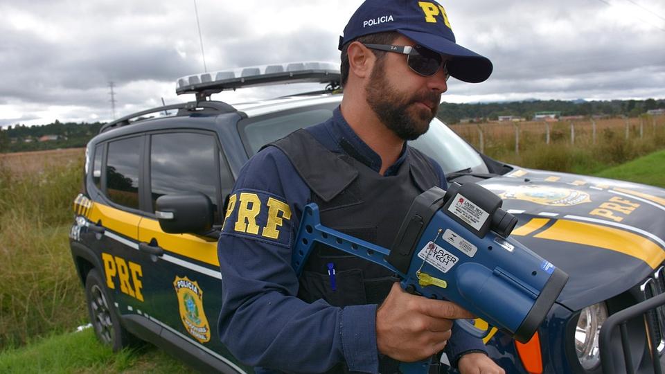 concurso prf: a imagem mostra policial rodoviário segurando equipamento que mede velocidade com viatura atrás
