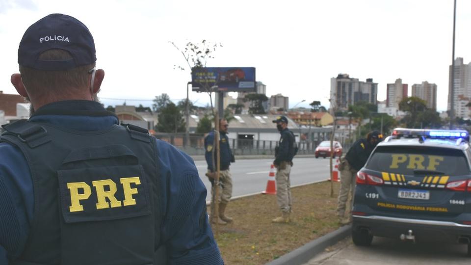 Concurso PRF: enquadramento nas costas de Policial Rodoviário Federal. De longe, é possível ver outros policiais e uma viatura da PRF
