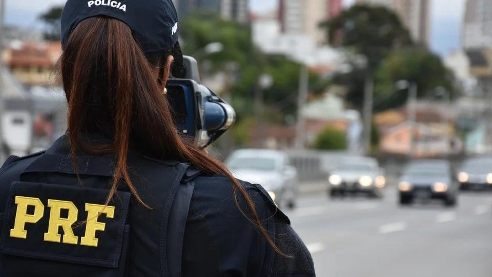 Provas do concurso PRF: profissional da PRF, de costas, usando aparelho para medir velocidade de carros