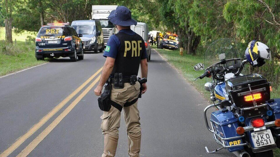 Concurso PRF: o que estudar para as provas: policial rodoviário olhando para a estrada com moto ao lado e caros ao fundo