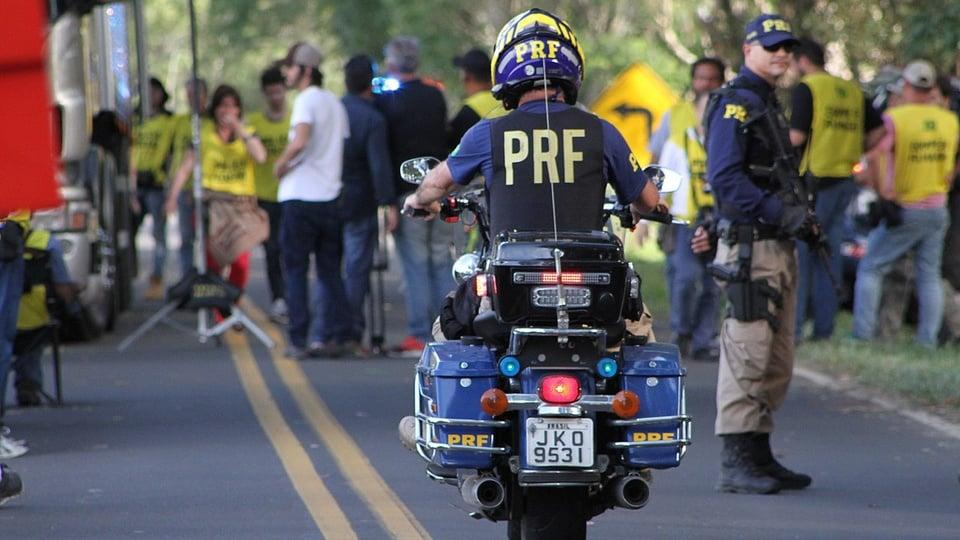 concurso prf: a imagem mostra policial em cima de moto em primeiro plano e ao fundo várias pessoas reunidas