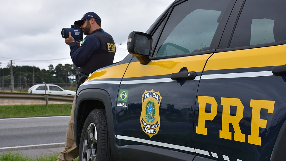 concurso PRF: a imagem mostra viatura da PRF em primeiro plano e ao fundo policial rodoviário segurando medidor de velocidade portátil apontado para a rodovia