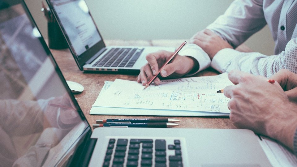 Processo seletivo Prodest - ES: dois notebooks sobre mesa; foco em mãos de duas pessoas segurando lápis sobre papel.