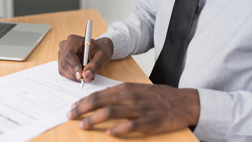 Concurso SAAE de Moema - MG: homem escreve em folha de papel
