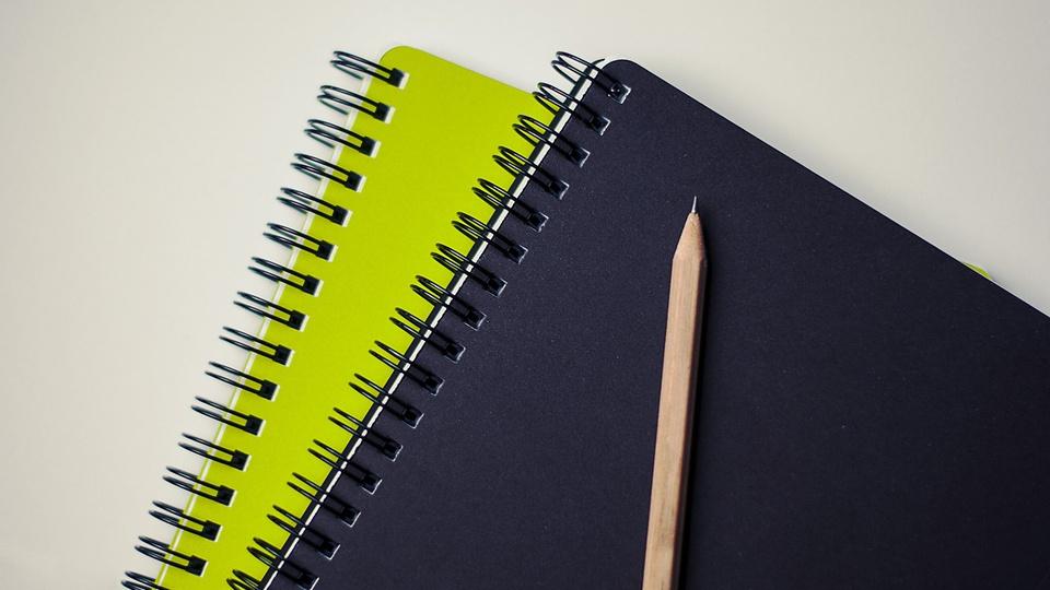 SAAEI de Ipuã: a imagem mostra caderno de capa verde sobre caderno de capa preta com lápis ao lado