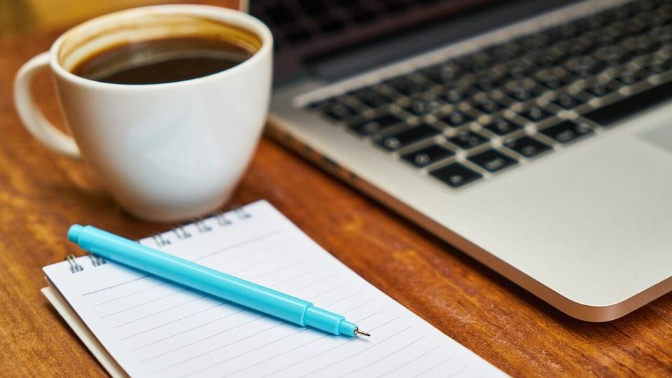 Concurso SAE de Ituiutaba: notebook sobre a mesa com caderno e caneca de café ao lado