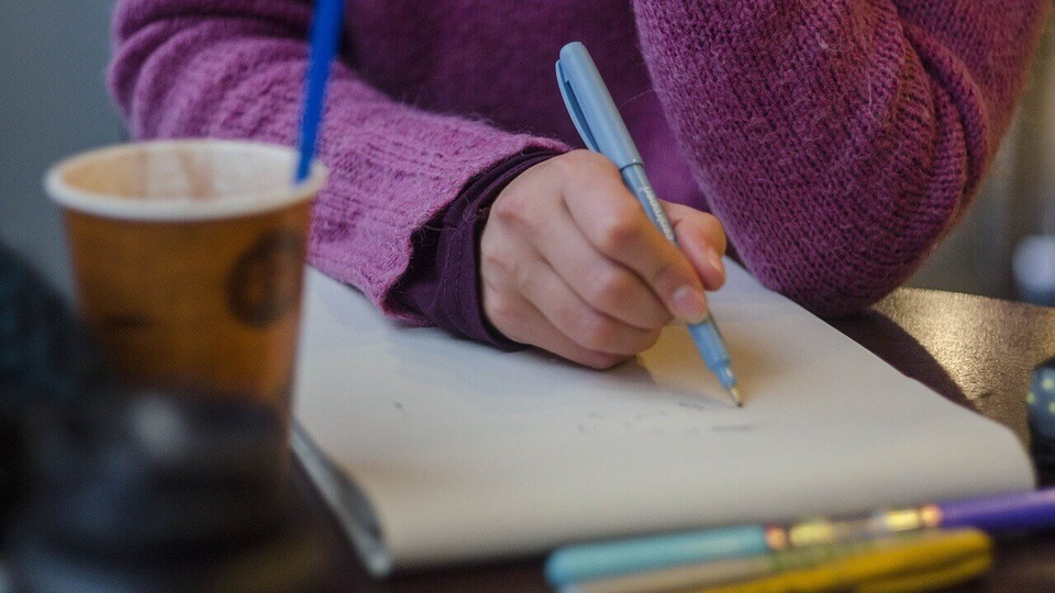 FUNSAÚDE de São Gabriel do Oeste - MS: pessoa escrevendo em um caderno. Na mesa há um copo de café.