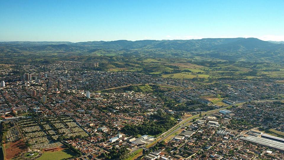 Concurso São João da Boa Vista - SP: a foto mostra a topografia de São João da Boa Vista, um panorama da cidade, vê-se casas, muito verde, serras
