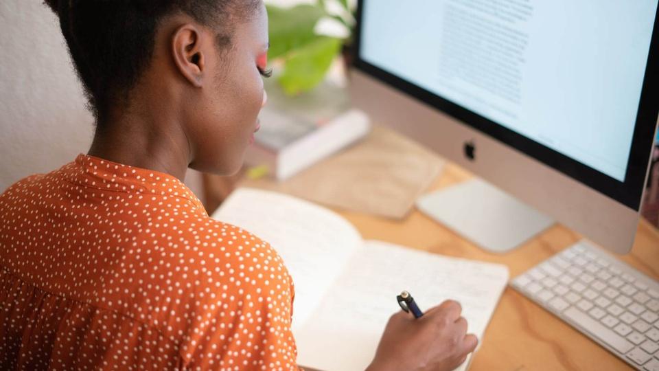 Concurso São José do Jacuri - MG: a foto mostra jovem negra de costas para a câmera escrevendo alguma coisa num caderno, sentada, à sua frente uma mesa e um monitor de computador ligado