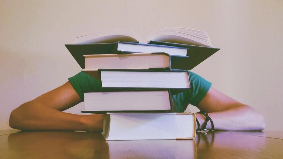 concurso seeduc rj: a imagem mostra pilha de livros sobre uma mesa com pessoa escondida atrás