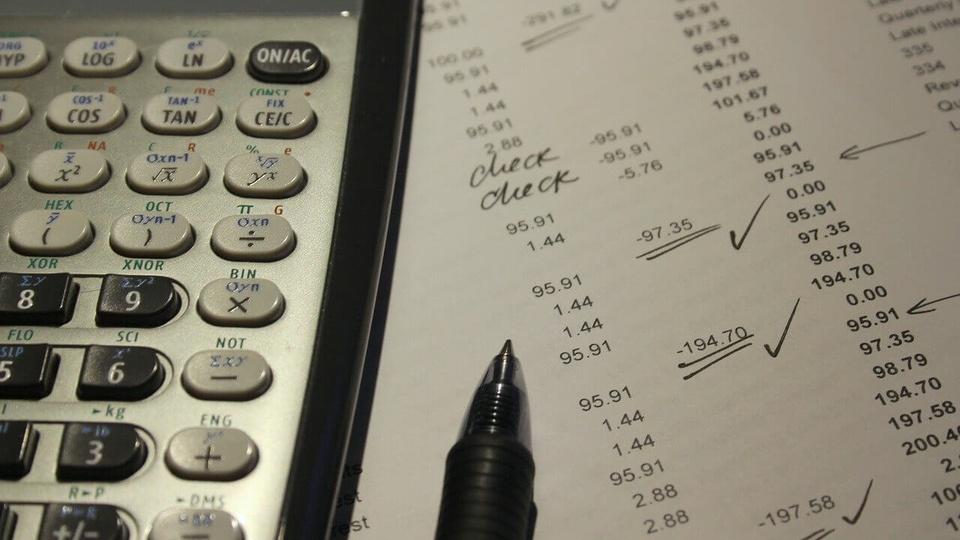Concurso Sefaz ES: a foto mostra uma calculadora, caneta e anotações de contabilidade em cima de uma mesa