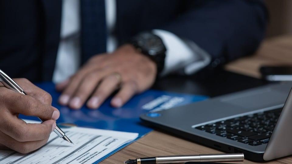 Concurso SEINFRA BA: a imagem mostra homem engravatado escrevendo algo em papel em frente a notebook