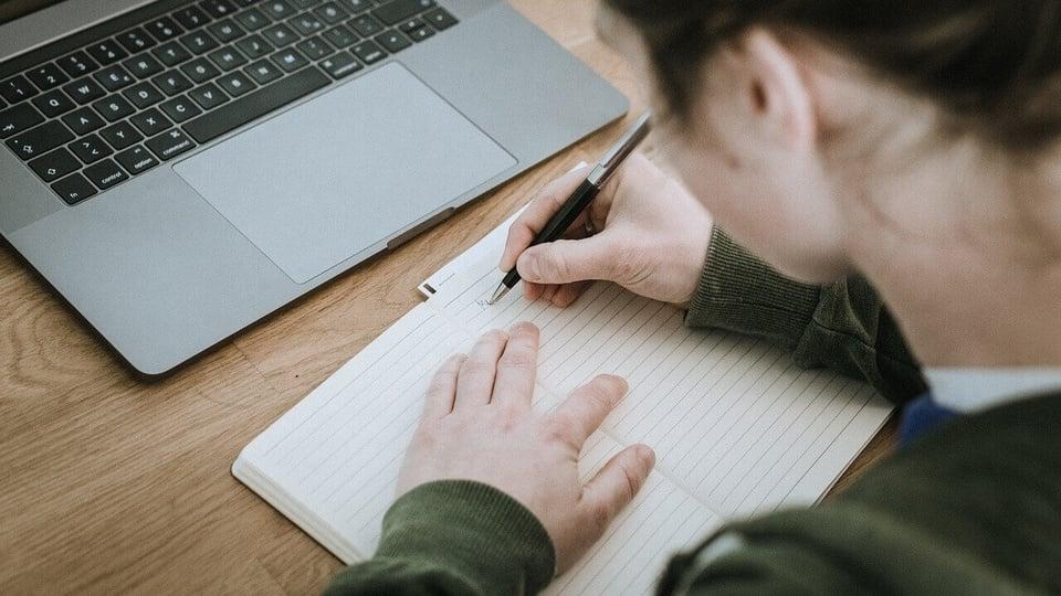 concurso sespa: a imagem mostra pessoa escrevendo em caderno em frente ao computador