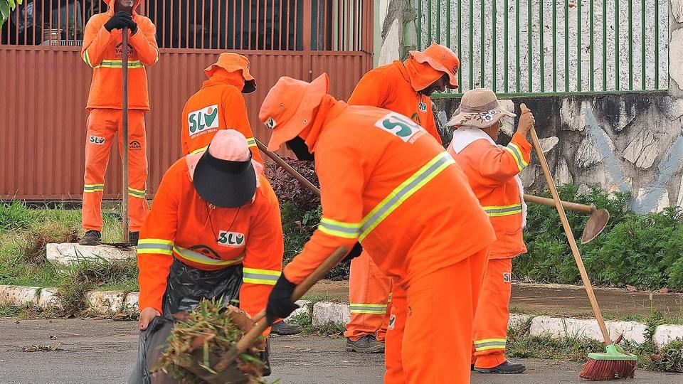 Concurso SLU DF: servidores fardados da limpeza pública do distrito federal realizando coleta de lixo na rua
