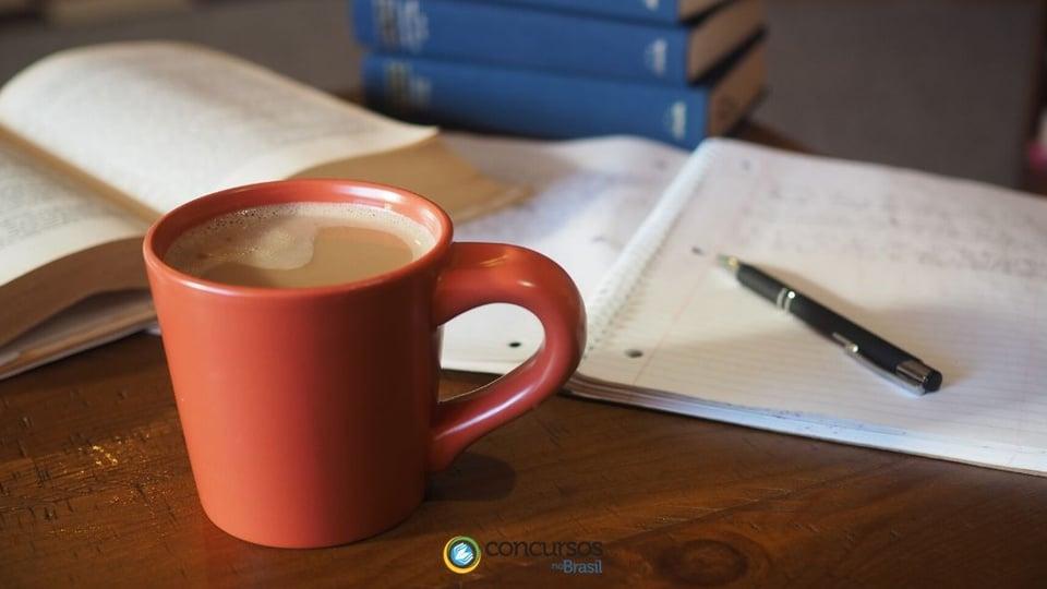 Concurso Prefeitura de Tamarana: a foto mostra xícara vermelha de café com leite, caneta, caderno e livros