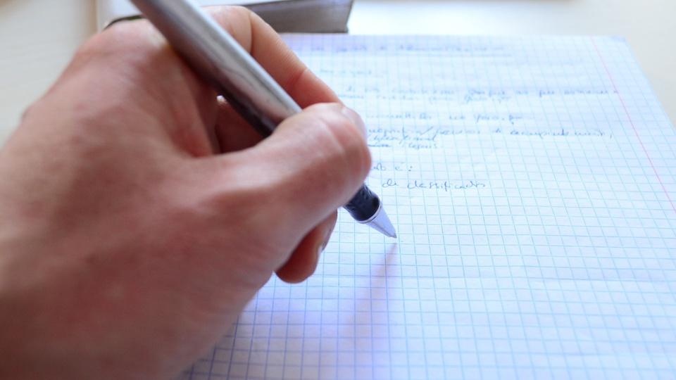 Concurso TJ GO Juiz 2021: foco em mão escrevendo em folha de papel