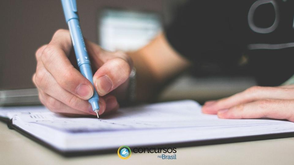 Concurso TJ SP: pessoa escrevendo num caderno