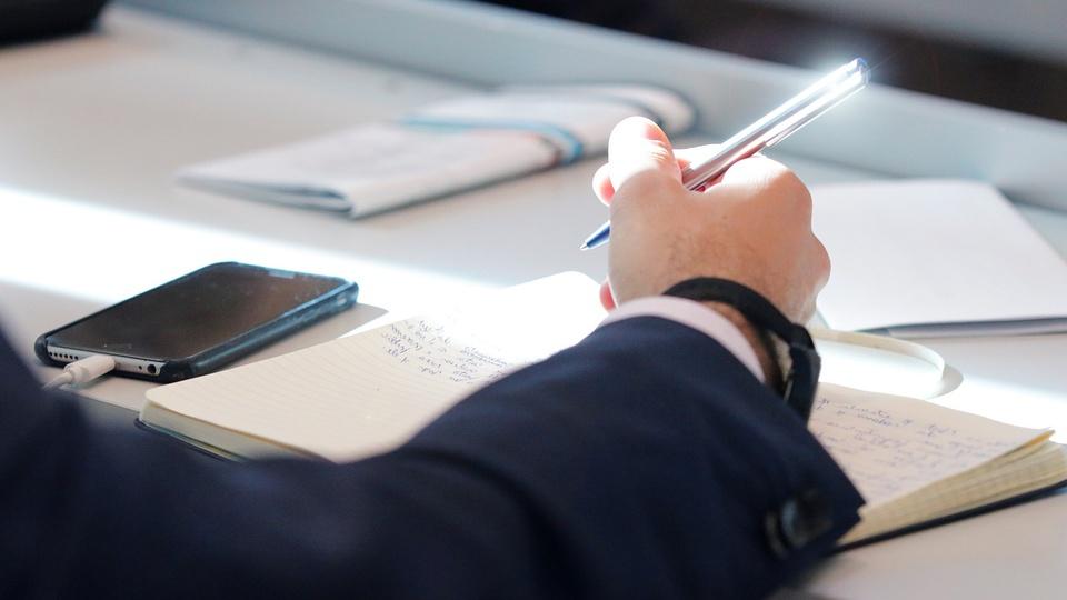 Concurso TRE ES: foco em mão masculina escrevendo em caderno