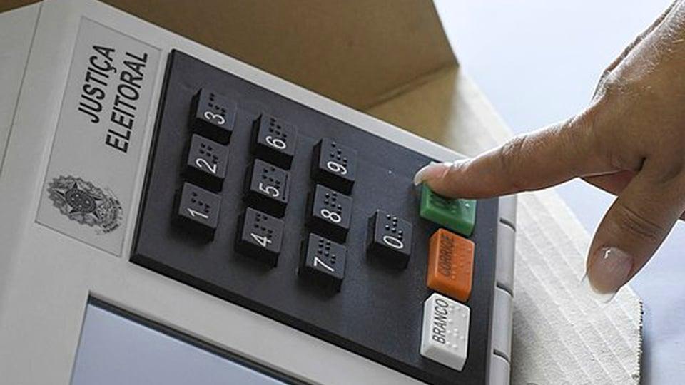 Concurso TRE RJ: pessoa apertando botão em urna eletrônica