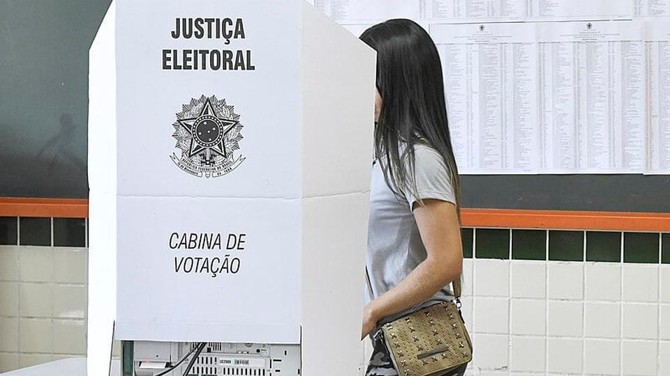 Eleitor que não justificar ausência não pode prestar concurso público: a foto mostra uma cabina de votação na urna eletrônica brasileira durante as eleições de 2018, ao lado da urna uma eleitora entrando na cabina para votar